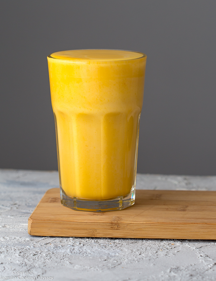 This yellow colour lassi served in a glass.