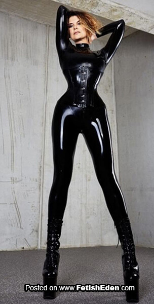 Sexy redhead in black latex catsuit with black latex corset and long black PVC boots