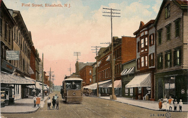 Hand-colored image showing street with trolley car on tracks in middle of the road. The street is lined with two and three story buildings, many with storefronts on the ground level. Children are gathered on the corners looking at the streetcar or the camera.