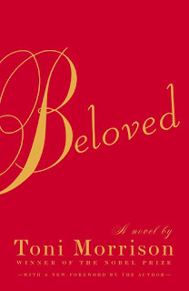 """""""Beloved"""" in cursive writing on a plain red background."""