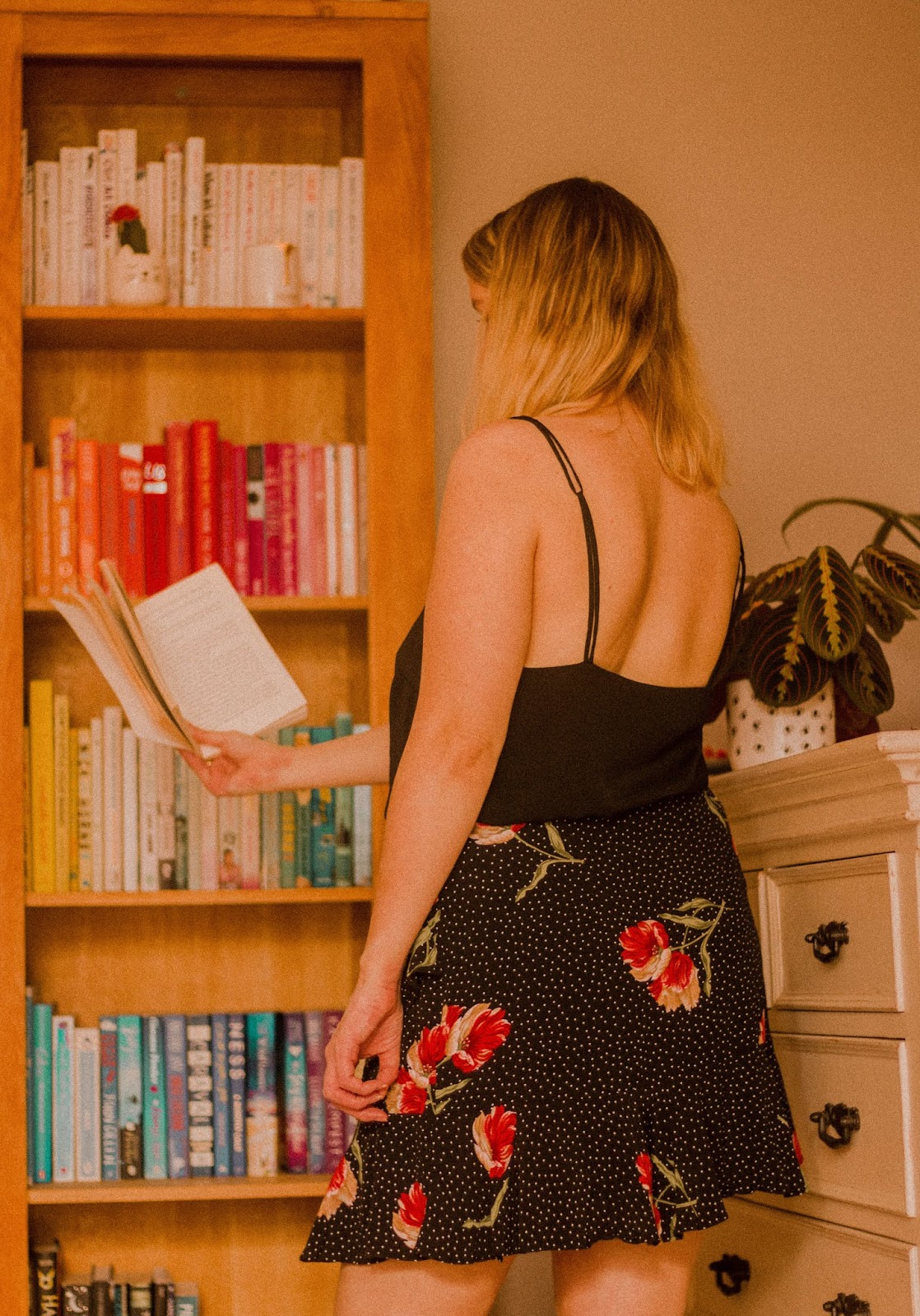 blonde girl stood reading in front of colourful bookcase full of books