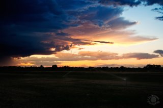 Professional quality landscape photograph of a farmer's field and sprinklers and a stormy sunset near Firth, Idaho by Cramer Imaging