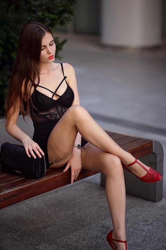 Czarne koronkowe body, spódniczka mini, cieliste pończochy ze szwem oraz czerwone buty