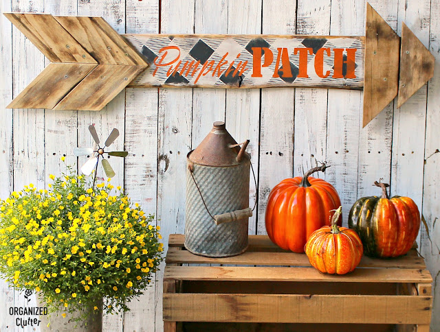 Photo of an arrow stenciled with buffalo checks and pumpkin patch.