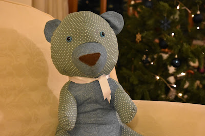 green teddy bear next to Christmas tree