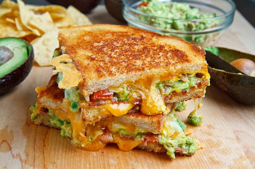 A buttery and toasty grilled cheese sandwich stuffed with cool and creamy guacamole, crispy bacon and melted jack and cheddar cheese. The crunchy crumbled tortilla chips in this grilled cheese pay tribute to the classic combination of tortilla chips and guacamole dip