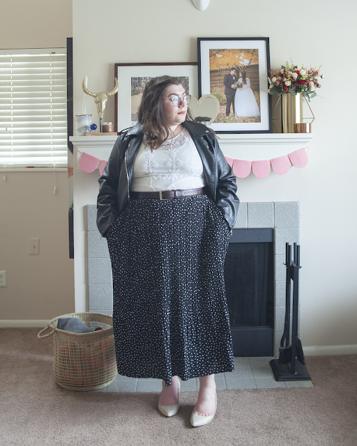 An outfit consisting of a black moto jacket over a white lace blouse tucked into a white on black dotted pleated maxi skirt and beige heels.