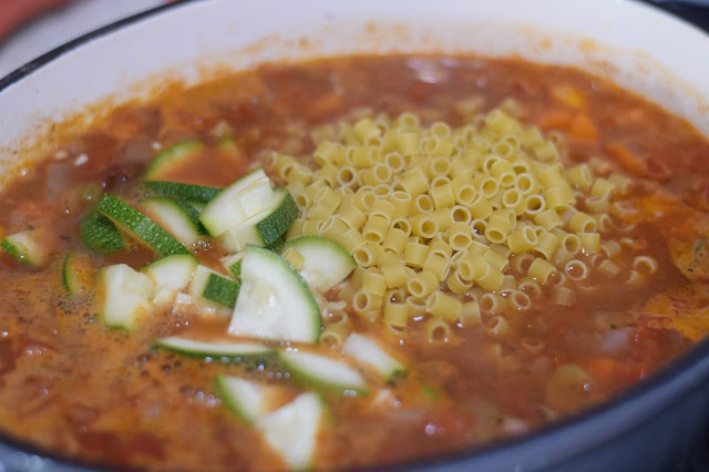 The pasta and zucchini being added to the minestrone soup.