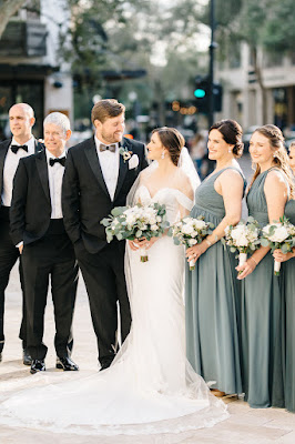 bride and groom smiling with bridal party