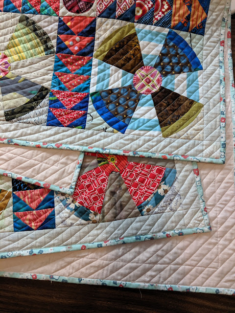 The light blue print makes a quiet binding that does not compete with the quilt blocks.