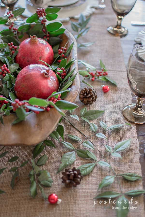 Christmas table with burlap runner, wooden dough bowl with pomegranites, and holly