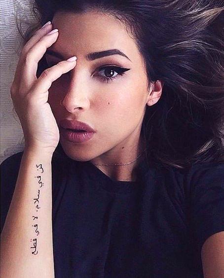 chica morena nos mira desde la cama, lleva tatuaje de letras araves en el antebrazo