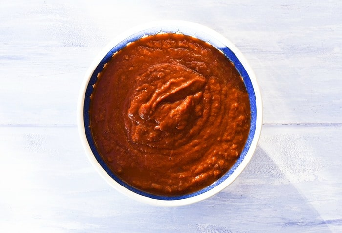 Homemade marinara sauce in a large bowl with a blue rim