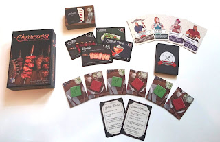 The game components next to the game box. The box has an illustration of several large skewers of various types of meat. The components show the food deck with a few cards face up, the action/reaction deck with a few cards face up, the six food request tokens (three on sim - the 'yes' side - and three on não - the 'no' side), and a basic rules and a turn actions card.