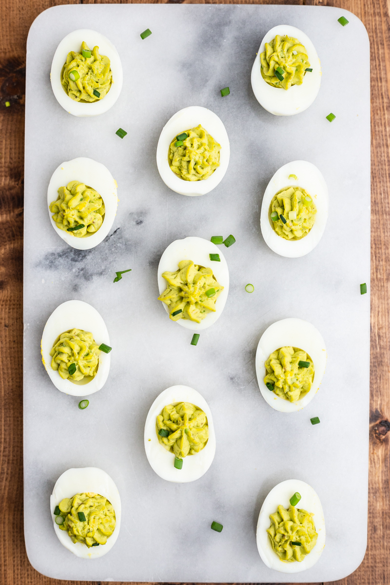 Overhead photo of Avocado Deviled Eggs on a marble background..
