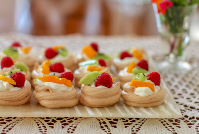 Food Lust People Love: These mini fruit-topped pavlovas are the perfect dessert for a dinner party or potluck.  The meringue bases can be made ahead of time then all you need to do is whip the cream and pop the fruit on top. No matter how it got there, pavlova is still a quintessential Australian or New Zealand dessert. A traditional fruit topping down under is passion fruit pulp but you can use whatever fruit you have on hand. Serve the mini fruit-topped pavlovas shortly after topping them as the cream will soften the meringues.