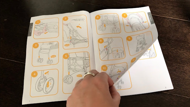 A hand looking through an instructions booklet with images for assembling the Joie Nitro pushchair