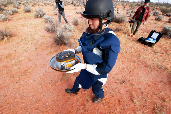 A JAXA technician carries Hayabusa2's sample return capsule back to a special container at the Woomera landing site in Australia...on December 6, 2020 (Japan Time).