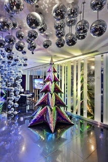 An inflatable iridescent Christmas tree standing by some windows. There are lots of silver baubles hanging from the ceiling.Jack Irving tree 2019.