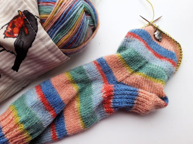 A partially-knitted sock in Stylecraft Head over Heels Red Pots yarn, with a small fabric bag featuring a Robin pattern containing a ball of yarn to the left