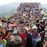 El perro arcoíris sonríe en Cice se pierde en la muralla china entre una multitud de turistas