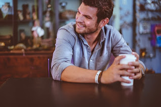 A men sitting alone in a cafe and smiling