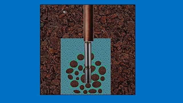 A imagem mostra o fundo do poço artesiano com água transparente e a rocha foi perfurada e revestida com canos de metal e PVC para proteger a pureza da água.
