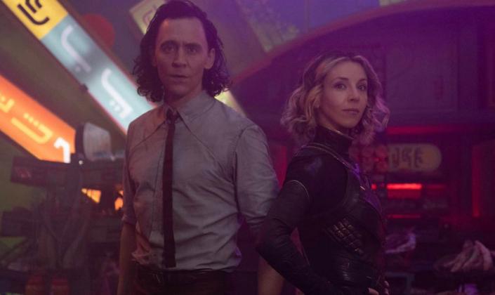 Imagem de capa: o Loki, interpretado por Tom Hiddleston, em uma camisa branca com gravata preta, em pé ao lado de Sylvie, uma mulher loira com uniforme verde com detalhes dourados e capa com pelos, em pé ao seu lado e ao fundo mesas destruídas e anúncios em cor néon coloridas com textos alienígenas.