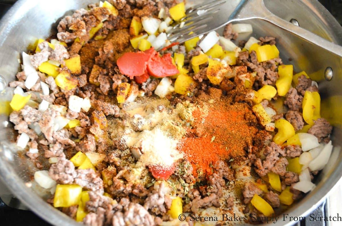Cooked hamburger, onion, garlic, diced bell pepper, tomato paste, chili powder, cumin, granulated Garlic, Smoked Paprika, Oregano, and Salt in a large pot.