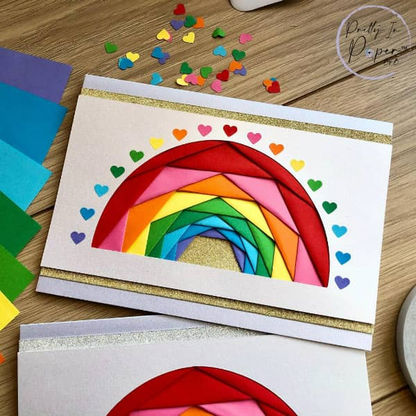 handmade iris folded rainbow greeting card displayed with extra papers and punched hearts in rainbow colors