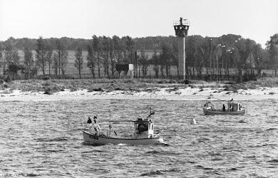 Ein Wachturm auf Land. Davor zwei Fischerboote(?), die verlassen auf dem Wasser dümpeln.
