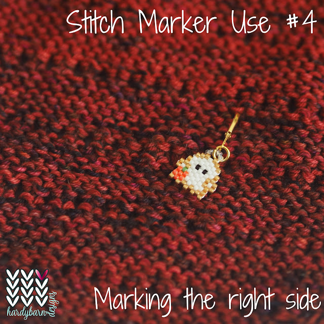 Red knitting with beaded ghost stitch marker