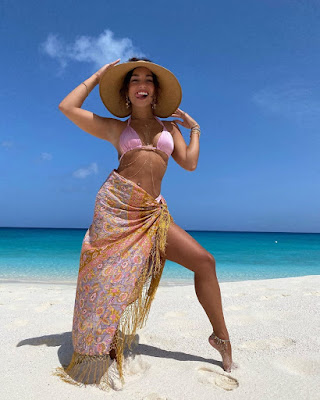 Vanessa Hudgens poking out her tongue in a pink bikini with embroidered beach wrap and sun hat