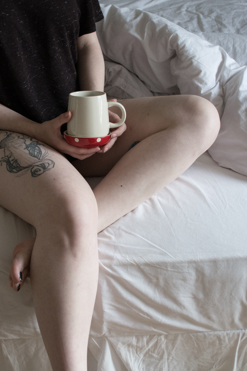 Girl with mushroom teacup coffee sitting on a bed