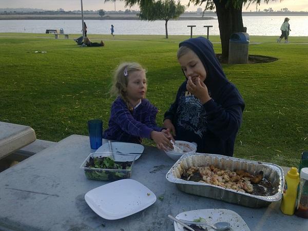 unsere Kinder essen selbst eingelegte Shrimps und Salat in der Bucht von San Diego, Californien