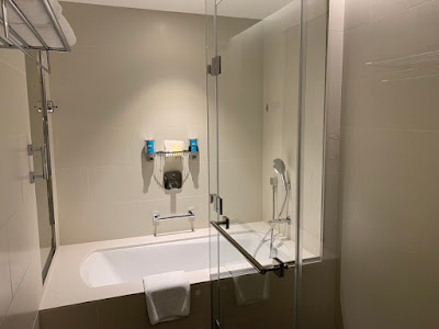 Bathroom at the Savvy Suite, comes with bathtub and amenities in bulk-sized containers