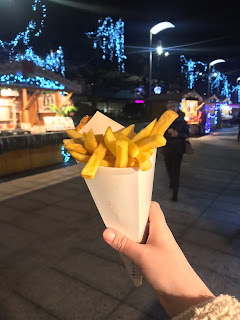 my hand holding up a cone of belgian fries with fairy lights in the background