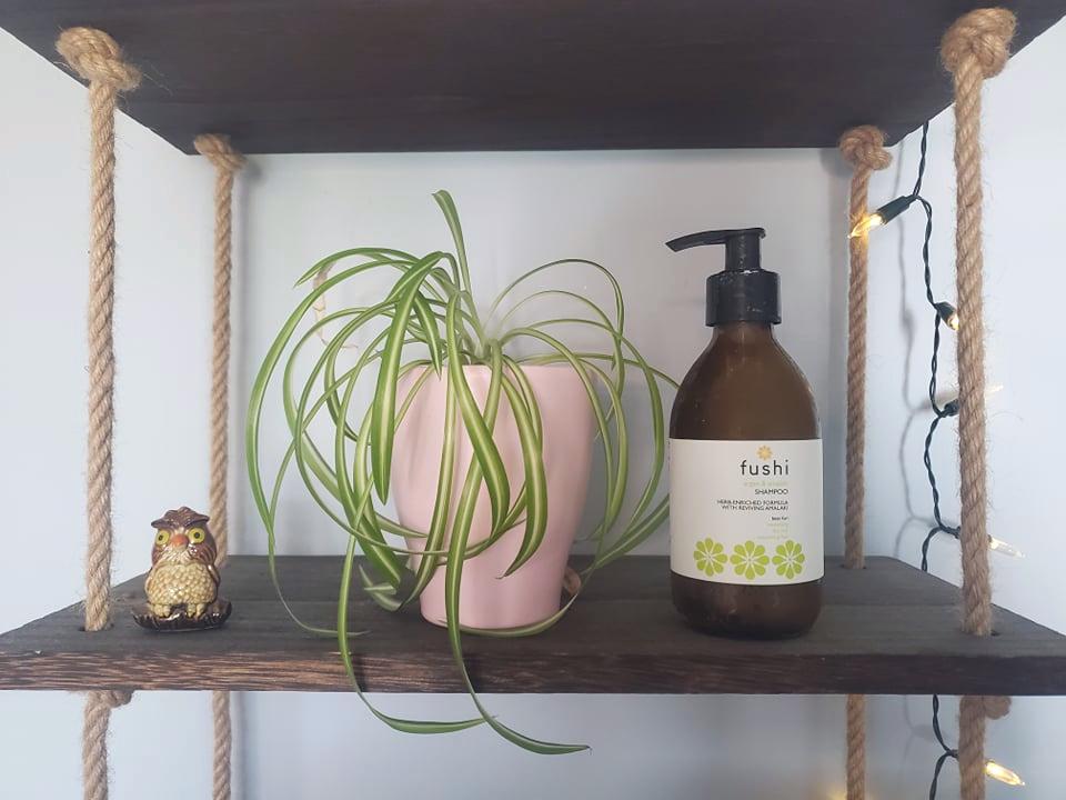 Fushi natural shampoo next to spider plant on hanging shelves