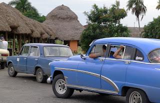 Kuba, Raststätte im Ranchónstil an der Strecke von Havanna nach Pinñar del Rio, davor Sammeltaxis, ein überfüllter hellblauer Straßenkreuzer und zwei Ladas.