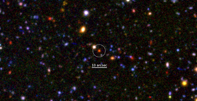 A blow-up of a small portion of the Subaru/XMM-Newton Deep Field.  The red galaxy at the center is a dying galaxy at 12 billion years ago.  Astronomers measured the motion of stars in the galaxy and found that the core of the galaxy is nearly fully formed. Credit: NAOJ/M. Tanaka