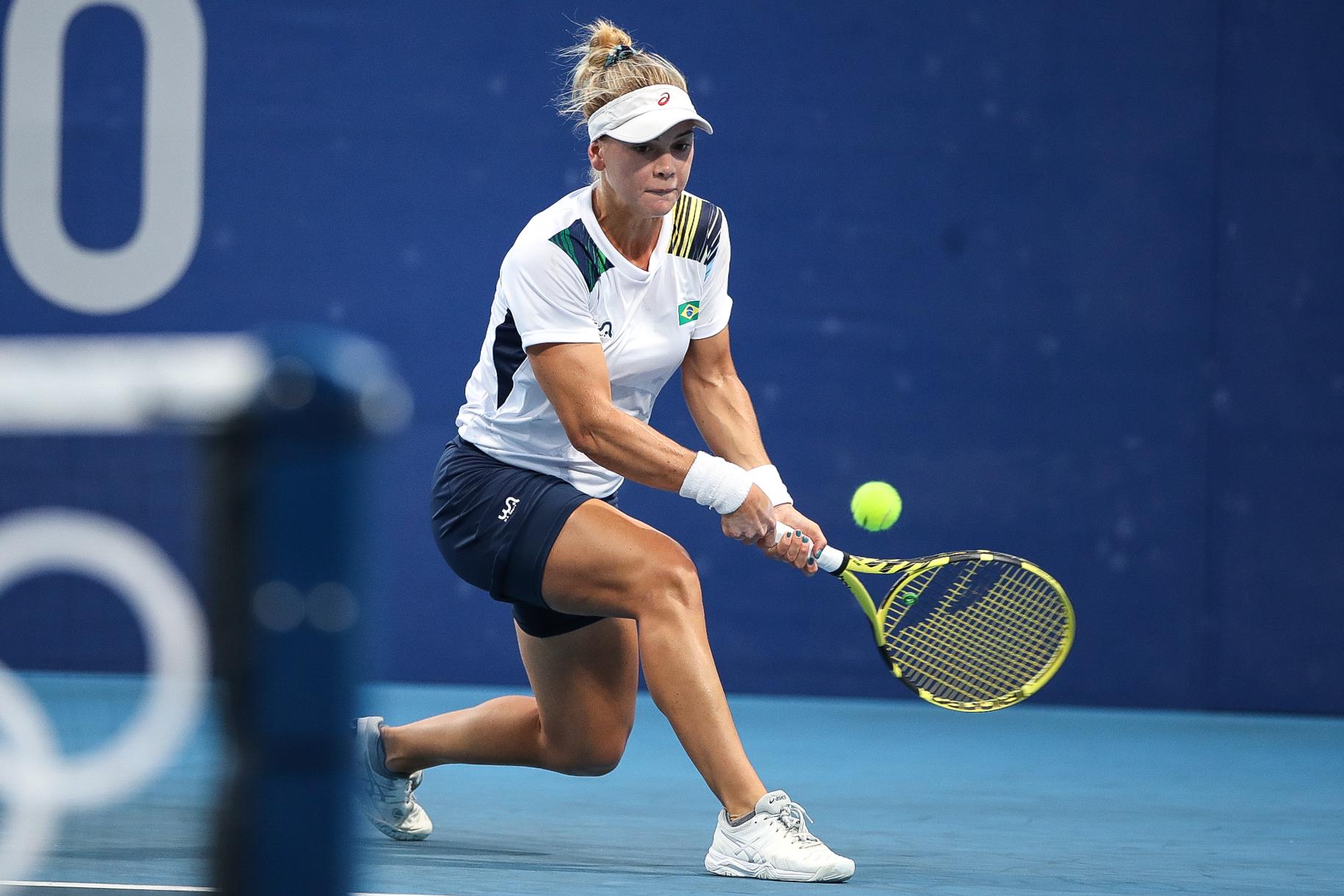 Laura Pigossi, de branco, com a raquete na mão, perto da bolinha