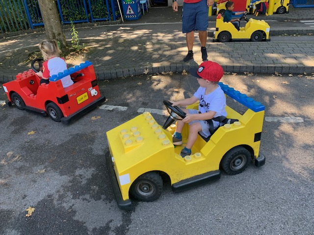 Boy driving a lego car at the driving school