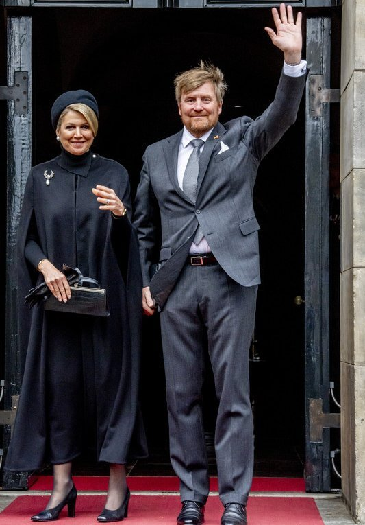Queen Maxima wore a black wool fur collar cape coat. Black leather handbag. Pearl drop earrings and diamond brooch. Gripoix earrings
