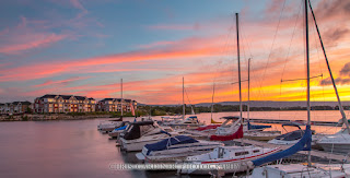 a colourful sunset scenic showing boats in the harbour, the shipyards development across the water, and a sky full of colourful clouds.