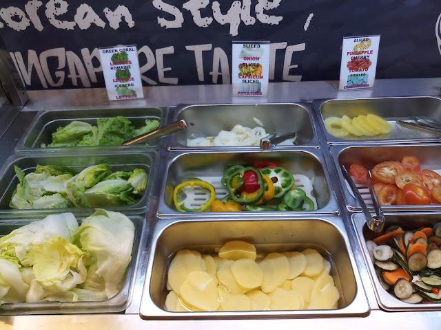 Buffet food: Green coral lettuce, Romaine lettuce, Iceberg lettuce, Sliced onion, Sliced capsicum, Sliced potatoes, Sliced pineapple, Sliced tomato, Sliced cucumber