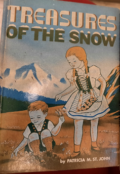 This is the original Treasure of the Snow cover featuring a girl and a boy in traditional swiss outfits playing in a field with mountains in the backgroud.