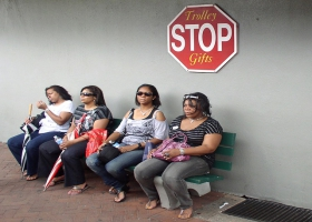 Women waiting sitting on a bench.