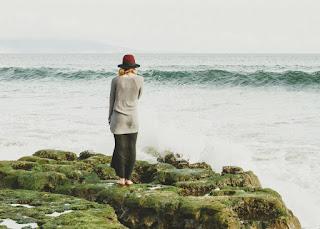 Femme sur un rocher au bord de la mer