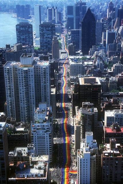 Perspectiva aérea de una calle de la ciudad de Nueva York a través de la cual la gente marcha con una bandera del orgullo de siete cuadras de largo