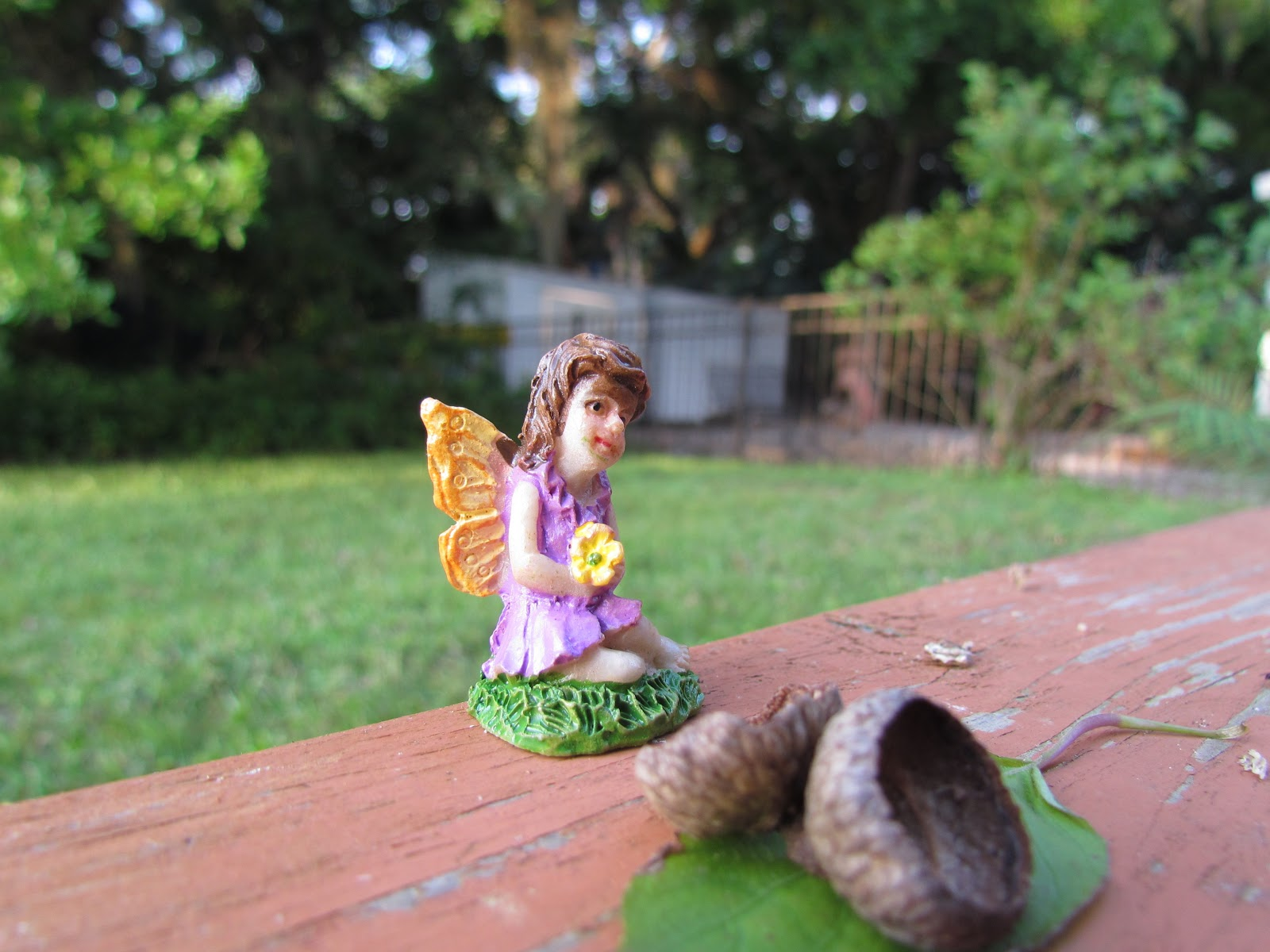 A tiny dark-haired fairy statue in purple garb with flowers sitting on the back porch with an acorn in nature